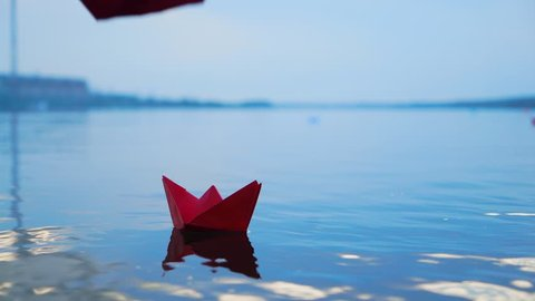 Woman's hand putting paper boat on the water. Beautiful summer sunset. Paper boat. Origami.