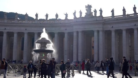 ROME, Italy- Dec.21, 2018: San Pietro Vatican Colonnade with Fountain and People walking on the Square