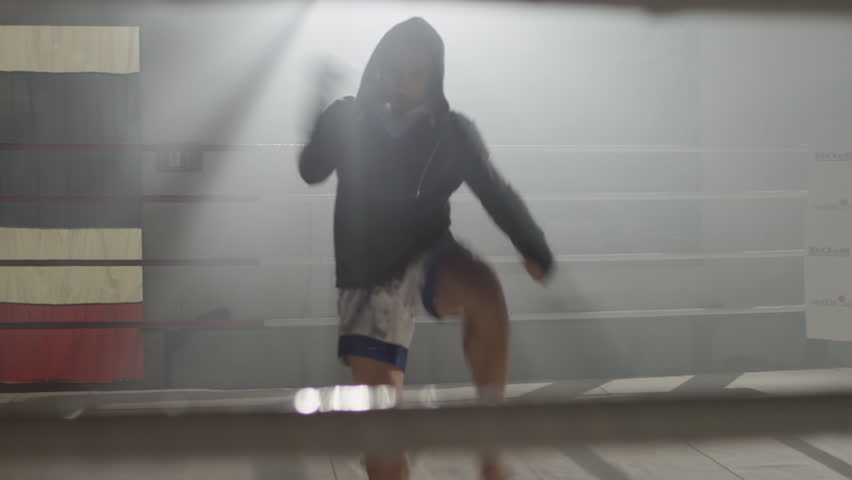 Muay Thai fighter in hoodie throwing punches at camera, shadow boxing, training in the middle of a foggy boxing ring backlit with flares in the background   Shutterstock HD Video #1021862749