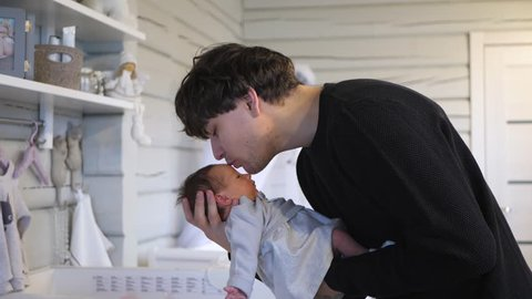 young father holding and kissing his new born infant baby