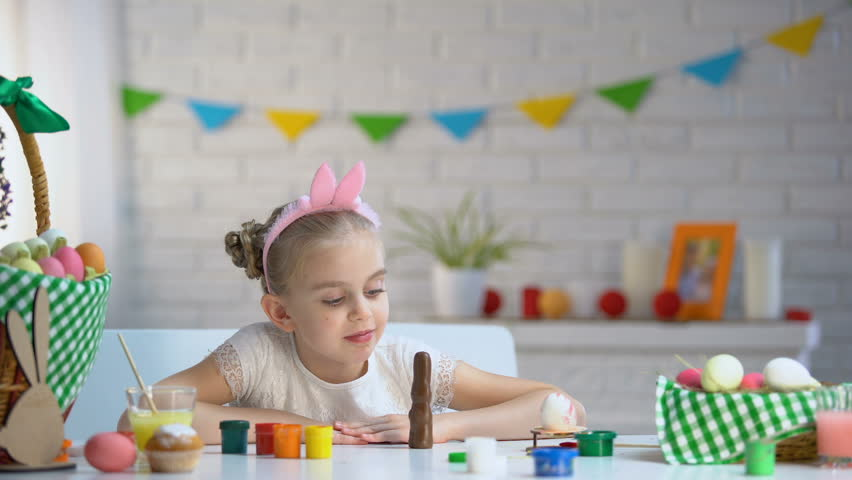 Little girl in cute headband smiling and posing at camera with chocolate bunny | Shutterstock HD Video #1021903189