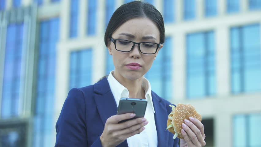 Young female manager eating unhealthy burger in hurry, checking news on phone   Shutterstock HD Video #1021904449