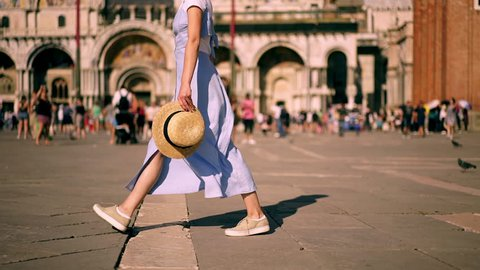 Slow motion effect of carefree female tourist with smartphone device and hat in hands feeling good walking at old town square. hipster girl turning around enjoying summer vacation holidays in Venice