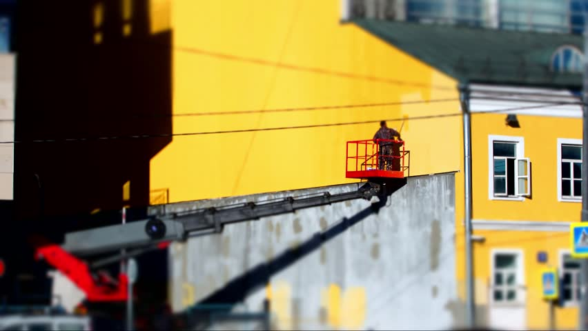 Paiting wall timelapse. Building restoration. Sky lift. Painter in the cradle of skylift paints the wall of an old building with yellow paint.