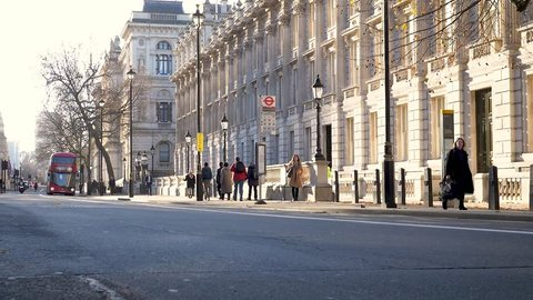LONDON, UK  - 4 DECEMBER 2018: A modern red double decker London bus pulling into a bus stop outside an anonymous government building in Whitehall.