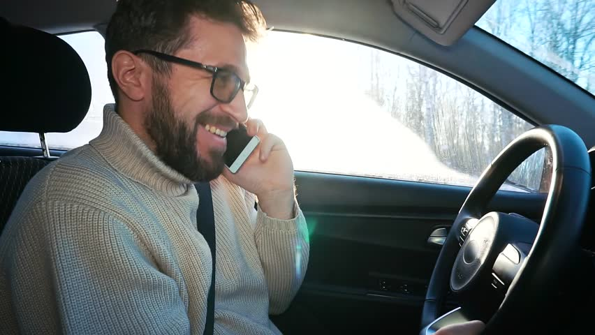 A man drives a car in winter on the highway between cities. He is talking smartphone and laughing. He is terrified, a car accident   Shutterstock HD Video #1022096239