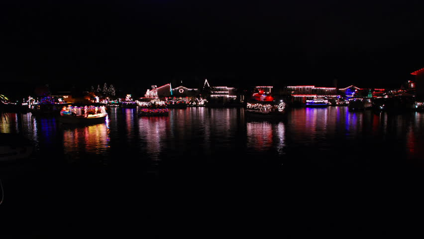 Boat parade on a lake with Christmas lights reflecting on the water - part one - HD.