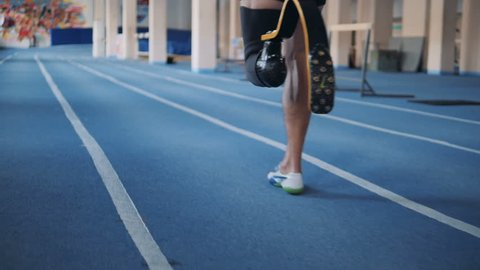 One man with bionic leg training on a running track, back view.