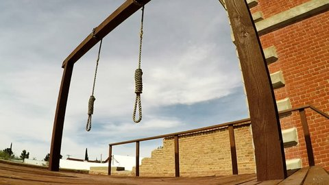 Tombstone, AZ / USA - August 1, 2018: Zoom in shot of two nooses hanging from a wooden gallows in Tombstone Arizona. Clip highlights Wild West justice and a violent form of execution from the past.
