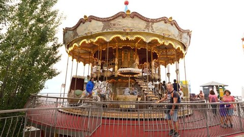 BARCELONA, SPAIN - AUGUST 17, 2018: Happy couple enjoy ride at vintage carousel, adult people walk to attraction. Classic amusement ride at Tibidabo theme park