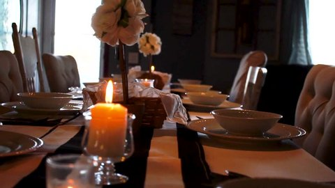 Fancy dinner settings in candlelit home dining room, Panning