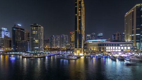 Aerial vew of Dubai Marina with shoping mall, restaurants, towers and yachts night timelapse, United Arab Emirates. Top view of canal with illuminated buildings and waterfront