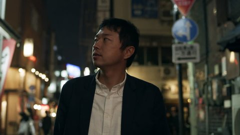 Japanese man looking around and exploring down a quiet alleyway with restaurants and shops with soft natural lighting at night. Medium shot on 4k RED camera.