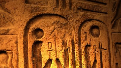 Ancient Egyptian Symbol of ten commandments or another object of ancient origin lit by candle