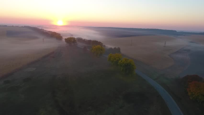Beautiful aerial view of the road with driving car, morning fields covered with fog at sunrise. Ukraine   Shutterstock HD Video #1022232019