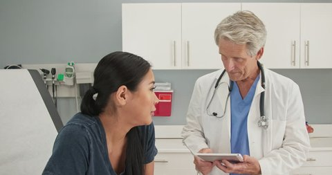 Older man doctor listening to medical history from Japanese woman in exam room while holding tablet computer. Senior Caucasian male medical professional in OBGYN office with patient. Slow motion 4k