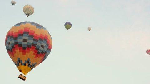 Hot air balloons flying over the rock landscape of Cappadocia, Turkey