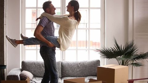 Happy couple renters owners tenants celebrate moving day in own flat, excited man husband holding carrying woman wife having fun among cardboard boxes package enjoy relocation into new home apartment