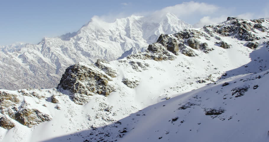 Wide shot POV AERIAL View of Mount Everest snowcapped cold rock mountains with sunny blue skies in Nepal and Tibet