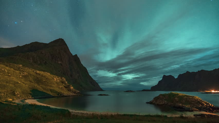4k Timelapse movie film clip of Aurora borealis in Lofoten islands, Norway. Aurora. Green northern lights. Starry sky with polar lights. Sea with sky reflection, stones, beach and snowy mountains. | Shutterstock HD Video #1022306839