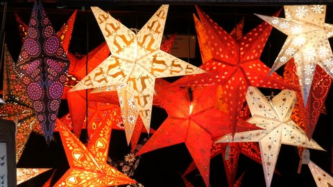 Beautiful decorative paper glowing Christmas stars lights on the Christmas market in Germany