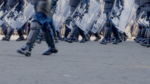 A march of riot police to protect the city