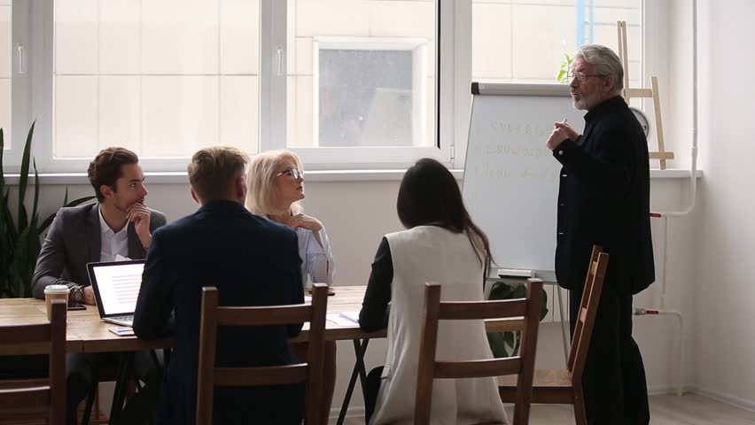 Senior executive leader coach presenter speak at meeting give business presentation lecture for corporate workers group, employees listen to old speaker explain training professional team at seminar | Shutterstock HD Video #1022373469