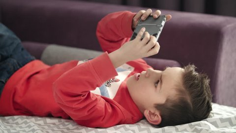 Boy playing mobile game on smartphone on sofa. Preschooler playing mobile phone. Kid using phone for gaming. Child playing video game at home