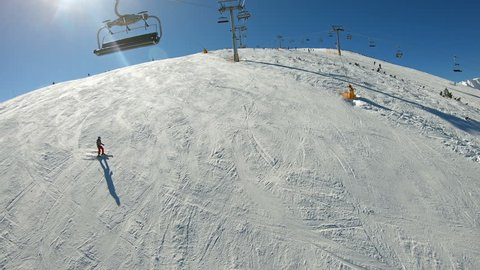 POV of riding the Ski Lift to the top of mountain summit Todorka on a sunny day in Bansko, Bulgaria