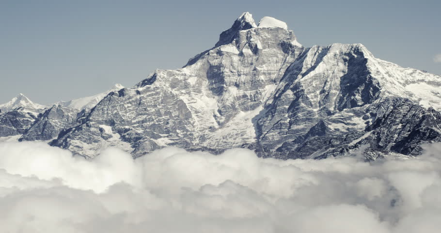 Mount Everest epic aerial wide shot panoramic view of snowcapped cold rocky mountains with clouds in Nepal near tibet with cloudy skies and fierce winds.