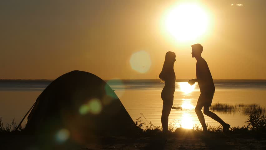Silhouettes of kneeled man proposing his beloved woman on the beach at sunset. Boyfriend putting engagement ring on happy surprised female's finger. Couple embracing in happiness