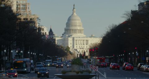 US Capitol Building in winter with traffic along Pennsylvania Avenue.