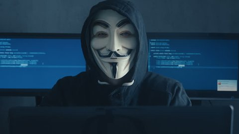 Cherkassy, Ukraine, January 10 2019: Dangerous Hacker Anonymous in mask of Guy Fawkes Showing Fuck You in dark room filled with display screens.