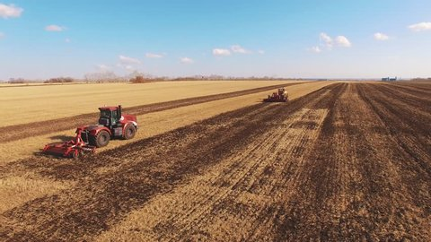 Two red tractors plow the field from a quadrocopter; the tractor has smoke coming from the pipe.