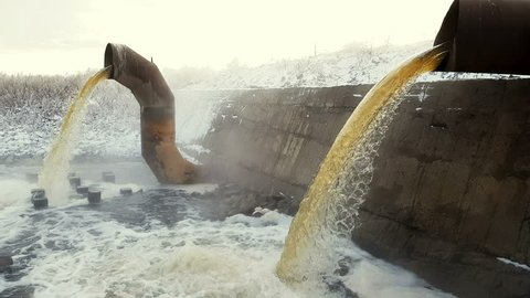 Wastewater from two large rusty pipes merge into the river in clouds of steam