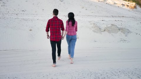 Couple of lovers walking on the each at sunset. Young couple walking up to the top of a sand dune embracing each other in love, Young couple in love walking on nature holding hand in hand.