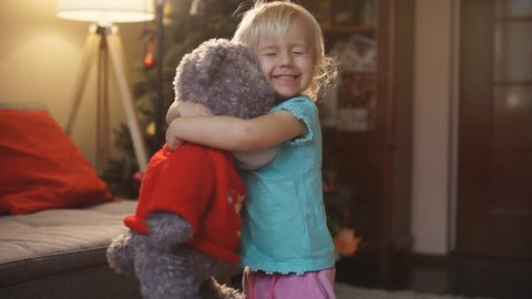 Portrait of expressive little girl hugging her plush bear friend, indoor shot. Little girl playing with teddy bear