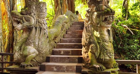 Old dragon statues decorated with traditional Hindu ornaments temple site in Ubud, Bali, Indonesia