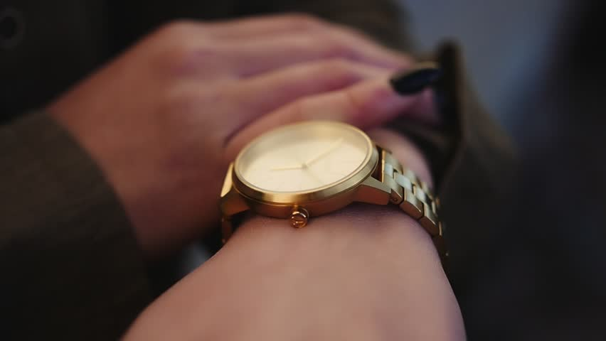 Woman with black nails checking time on gold watch