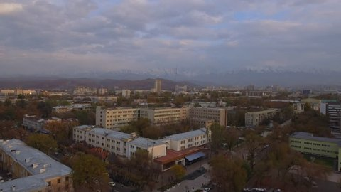 Beautiful autumn aerial view of the old city center on the background of snow-white mountains. Almaty, Kazakhstan