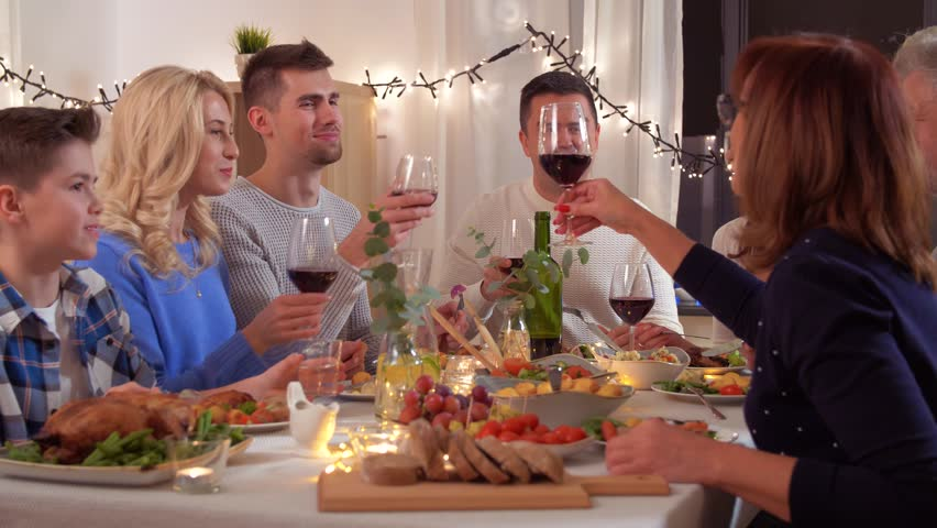 Celebration, holidays and people concept - happy family having dinner party, drinking red wine and toasting at home | Shutterstock HD Video #1022556409