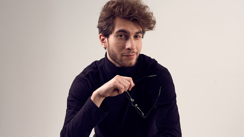 Fashion portrait of handsome elegant man with curly hair wearing black turtleneck and glasses on gray background in studio | Shutterstock HD Video #1022577859