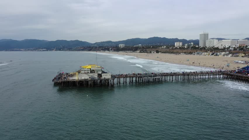 Arial view of Santa Monica pier in Los Angeles, California on an overcast day with the city and coastline in the background   Shutterstock HD Video #1022586499