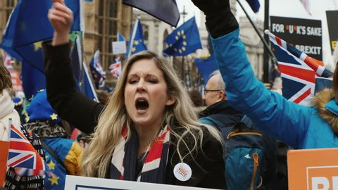 LONDON, circa 2019 - Slow motion shot of a BREXIT supporter holding a flag and banner and passionately defending her views in London, England, UK