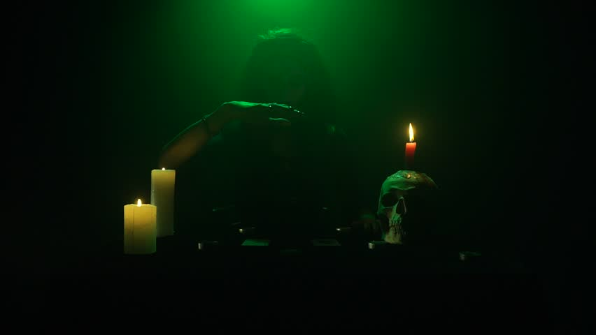 Evil witch sitting at the table with candles and a skull, and levitating a medallion | Shutterstock HD Video #1022598529