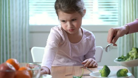 Little girl do not want to eat vegetables and dislike taste of broccoli and spinach. The concept of healthy baby food