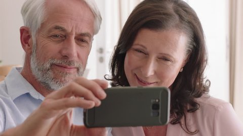 happy middle aged couple using smartphone having video chat waving at grandchildren enjoying online communication relaxing retirement home