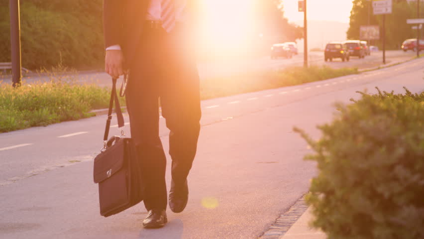 SLOW MOTION, SUN FLARE, LOW ANGLE: Unrecognizable sad man in a suit walking down the street at sunset. Young businessman in despair slowly walking along the sunlit road with his briefcase in hand. | Shutterstock HD Video #1022645119