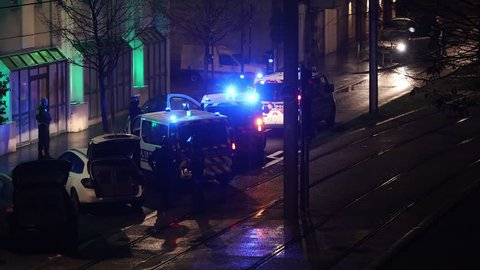 Bordeaux, France - January 2019 : French policemen standing around French police vehicles parked with blue lights and lighted sirens on during yellow vests movement and riots in France at night