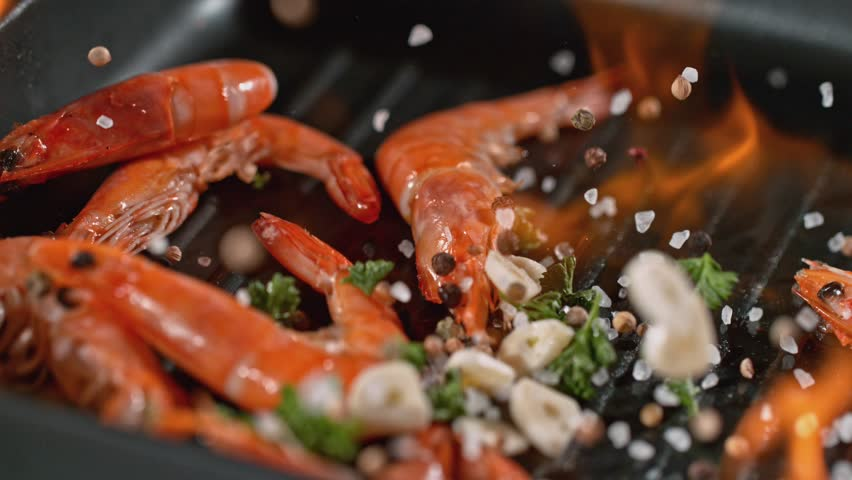Super slowmotion footage of throwing fresh prawns and seasoning on ignited pan, 1000fps 4k | Shutterstock HD Video #1022667829